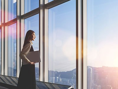 Business woman looking out window in high rise building