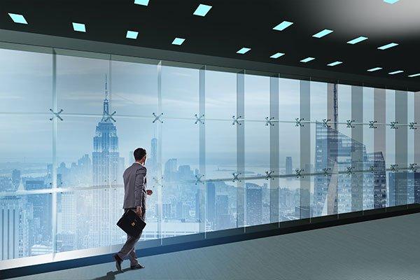 Man walking in building hallway with smart lighting